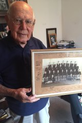 Eric Tweedale holding a photo of the 1946 Australia team.