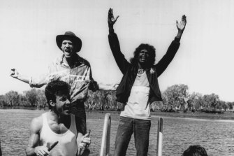 Midnight Oil's Peter Garrett and Rob Hirst with the Warumpi Band's George Rrurrambu (deceased)  performing at Yellow Water (Ngurrungurrudjba) on the South Alligator River at Kakadu during Blackfella/Whitefella Tour in 1986.