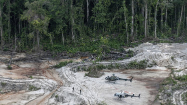 Ibama inspectors walk through an area affected by illegal mining after landing in Munduruku indigenous lands in Para state in Brazil's Amazon basin.