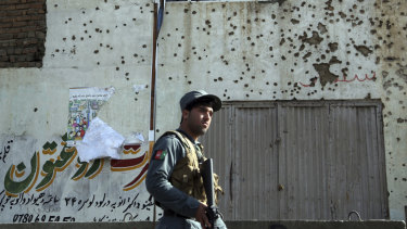 An Afghan security officer inspects the site of suicide attack near the election commission office in Kabul in October.