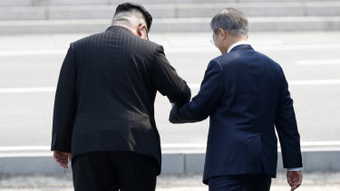 North Korean leader Kim Jong-un leads South Korean President Moon Jae-in across the military demarcation line to the North side of the border.