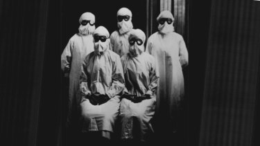 Group portrait of medical workers in protective gear during 1919 influenza epidemic.