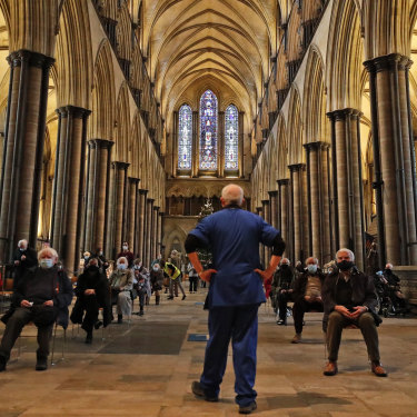 A medic monitors people who sit and wait after receiving their vaccine at Salisbury Cathedral.