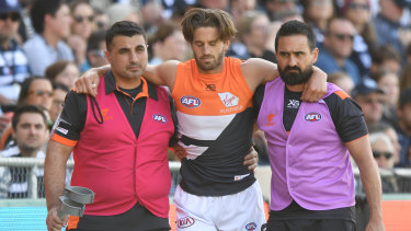 Ward is helped from the field after suffering a season-ending knee injury against Geelong.