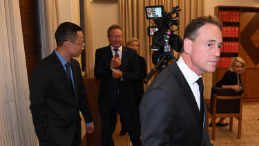 Health Minister Greg Hunt walks away from Chinese consul-general Zhou Long and Andrew Forrest after the press conference.
