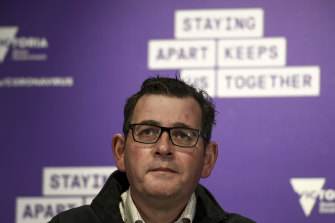 Victorian Premier Daniel Andrews in front of the Staying Apart Keeps us Together slogan.