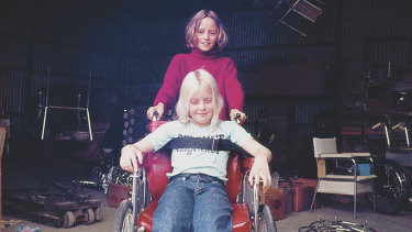 As a child playing in her father's wheelchair with brother Hugh.