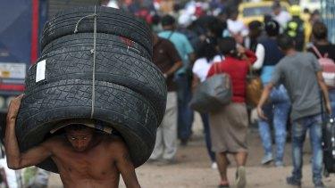 A man carries a set of used tyres into Venezuela through a blind spot on the border near the Simon Bolivar International Bridge in La Parada, Colombia.