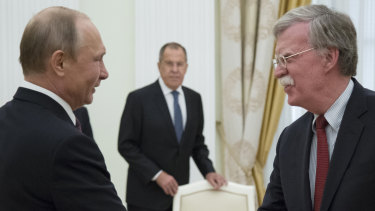 Russian President Vladimir Putin and US National Security Adviser John Bolton greet each other in Moscow last week.