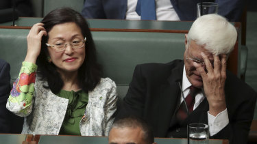 Crossbench MP Bob Katter covers his face while sitting next to Liberal MP Gladys Liu.
