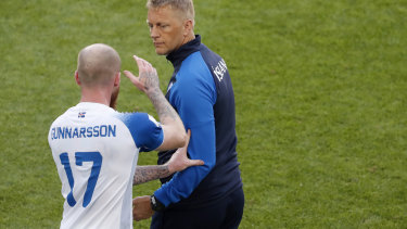 Cool as ice: Iceland's Aron Gunnarsson grabs the arm of coach Heimar Hallgrimsson.