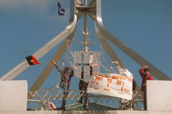 Protestors place flags on the Australian coat-of-arms at the front of Parliament House
