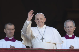 Pope Francis waves to the crowd after delivering the Christmas day blessing.