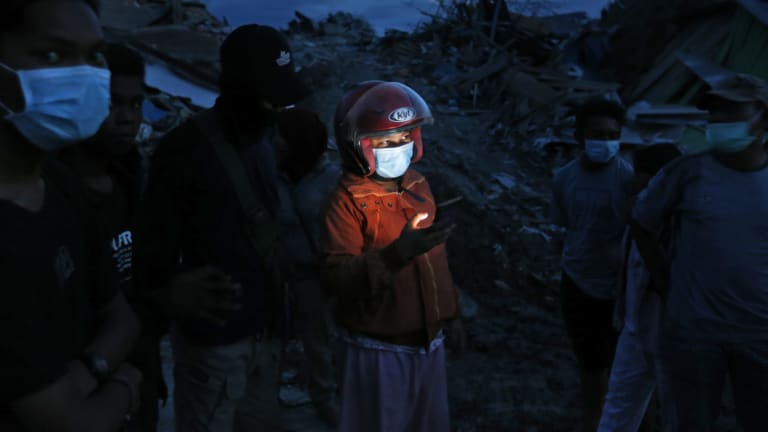A woman uses her mobile phone in Petobo neighbourhood, which was wiped out by earthquake-triggered liquefaction in Palu.