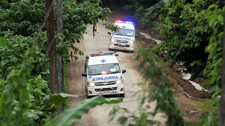 Ambulances carrying the 10th and 11th rescued drive away from Luang cave.