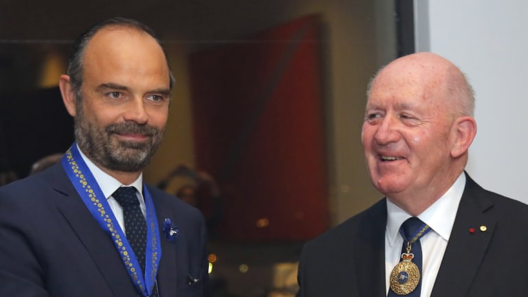 Australian Governor-General Sir Peter Cosgrove, right, shakes hands with French Prime Minister Edouard Philippe after awarding him with the Honorary Officer of the Order of Australia at the Australian Embassy in Paris.