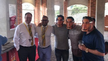Cricket South Africa executives Clive Eksteen and Altaaf Kazi pose with fans in Williams masks on Friday.