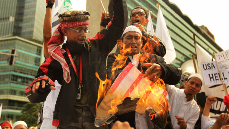 Protesters from Indonesia's hardline Islamic Defenders Front burn a poster of a US flag in 2012 to protest against the movie <i>Innocence of Muslims</i>.
