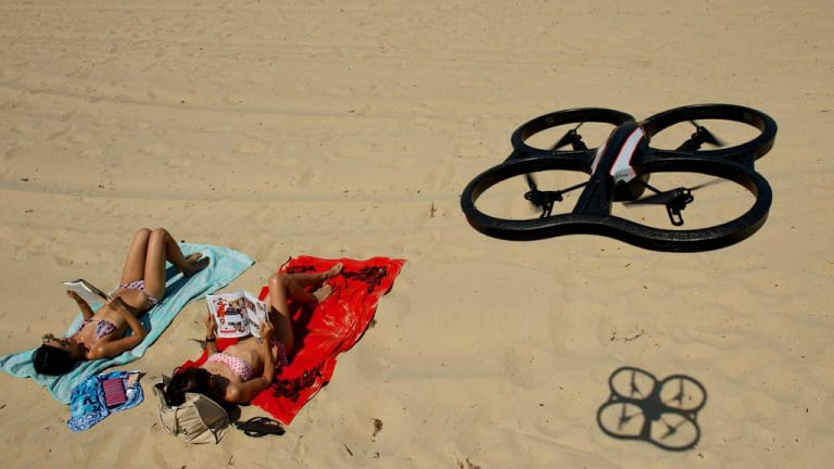 A remote controlled drone helicopter above sun bathers.