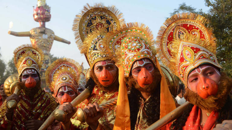 Hindus dressed as  Lord Hanuman pose during a religious procession.