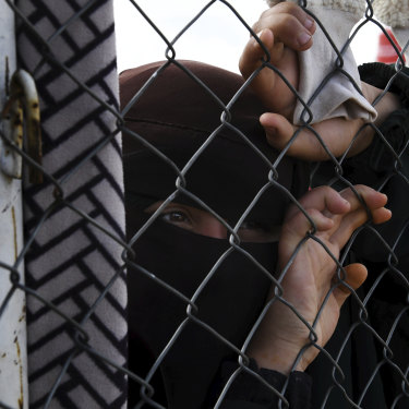 An Islamic State woman at the fence line of the foreign section of al-Hawl camp in Syria.