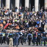 Protesters face-off with police on the steps of the Shrine of Remembrance.