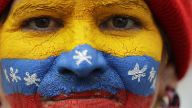 Her face painted in the colours of the national flag, a supporter of opposition leader Juan Guaido, Venezuela's self-proclaimed interim president, waits for his arrival in Los Teques on the weekend.