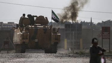 Turkish-backed forces cross the border into Syria onm an armoured personnel carrier.