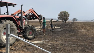 Tom Sheather (foreground) helps his uncle repair fences on his family's burnt farm.