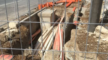A pit near the intersection of the Federal Highway and Flemington Road in Canberra, where electrical cables appear to be installed just a few millimetres below ground level.