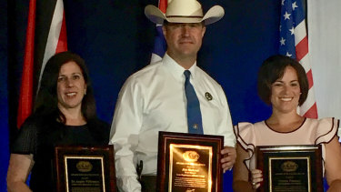 Department of Justice official Angela Williamson receives an award from the International Homicide Investigators Association alongside colleagues James Holland and Christie Palazzolo.