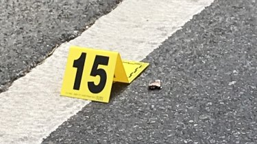 What appears to be the remnant of a bullet lies near a police marker on Mary Street.