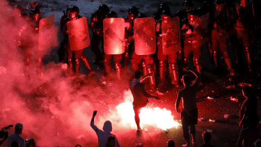 A man kicks a flare at riot police during protests outside the government headquarters, in Bucharest, Romania.