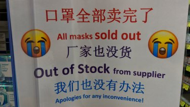 Signs written in English and Chinese at a Chemist Warehouse in the CBD tell customers the store is out of masks.