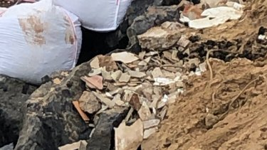 Asbestos and other building waste has been unearthed along Wamberal beach following severe erosion.