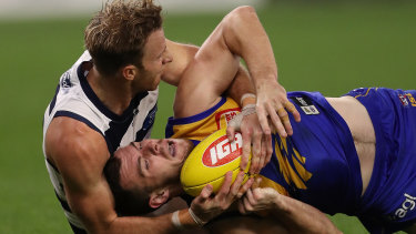 Rough and tumble: Geelong's Lachie Henderson tackles West Coast's Luke Shuey.