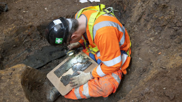 An archaeologist examines a coffin plate at the St James' cemetery.