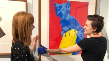 Rebecca Richards, left, and Emilie Patteson,  from the Australian Parliament House art collections team check Meow, a work by Maria Kozic, on display in the Imprint exhibition.