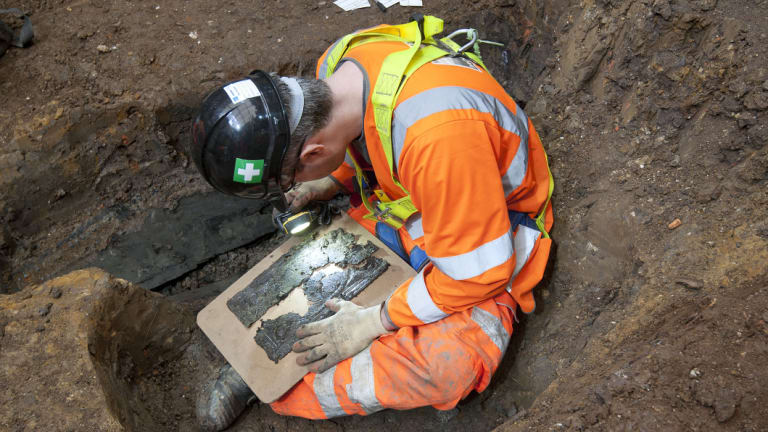 An archaeologist examines a coffin plate at a St James burial ground.