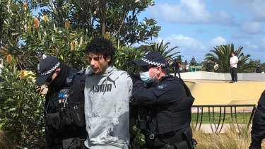 Victoria Police members arrest a protester along the St Kilda foreshore on Saturday, with children at a nearby skate bowl watching on.
