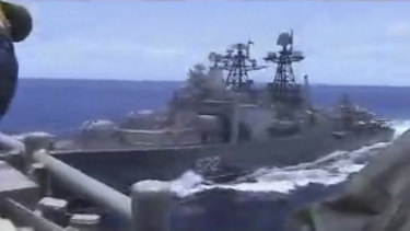 In this image from video provided the Russian destroyer, left, sails very close to the USS Chancellorsville.