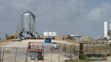 Crews working around SpaceX's Starhopper rocket at the company's launch facility.