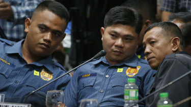 Philippine police officers Jeremias Pereda, Jerwin Cruz and Arnel Oares talk during a senate hearing on the killing last year.