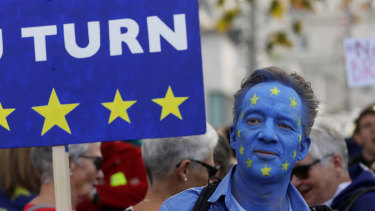 A demonstrator wears face paint in a European Union flag design as he holds a sign reading 'A EU TURN' ahead of the anti-Brexit People's Vote march, in London, UK.
