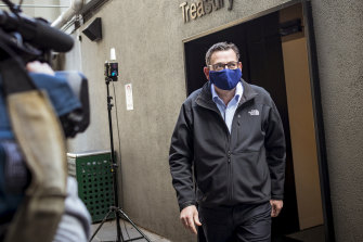 Daniel Andrews departs the daily COVID-19 press conference wearing a mask on Sunday.