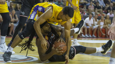 On the loose: Kevin Lisch of the Kings scraps for the ball with Jordair Jett of the Hawks.