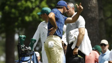 Battle: Jason Day holds his back on the fourth tee at Augusta.