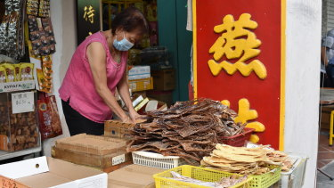 A vendor wearing a face mask prepares to display traditional Chinese medicinal products.