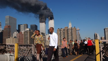 People walk across the Brooklyn Bridge as smoke billows from the twin towers on September 11, 2001. Walking was the only way out of the city that day.