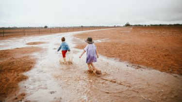 Dust to mud: the Paine children enjoyed Sunday's changing weather fortunes.